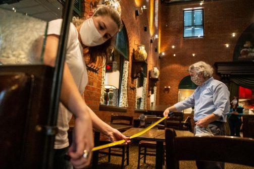 Team members measuring six feet between tables